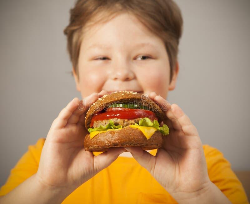 A criança come o hamburguer no fundo cinzento Criança masculina com Hamburger fotografia de stock royalty free