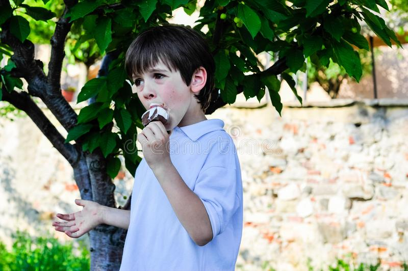 a criança come um gelado na máscara de uma árvore imagem de stock
