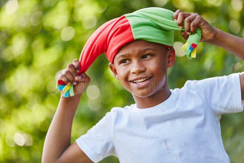 Criança como o arlequim com o tampão do ` s do tolo fotografia de stock royalty free