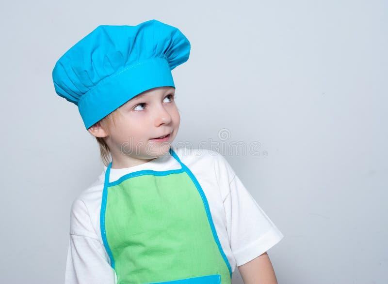 Criança como um cozinheiro do cozinheiro chefe imagem de stock