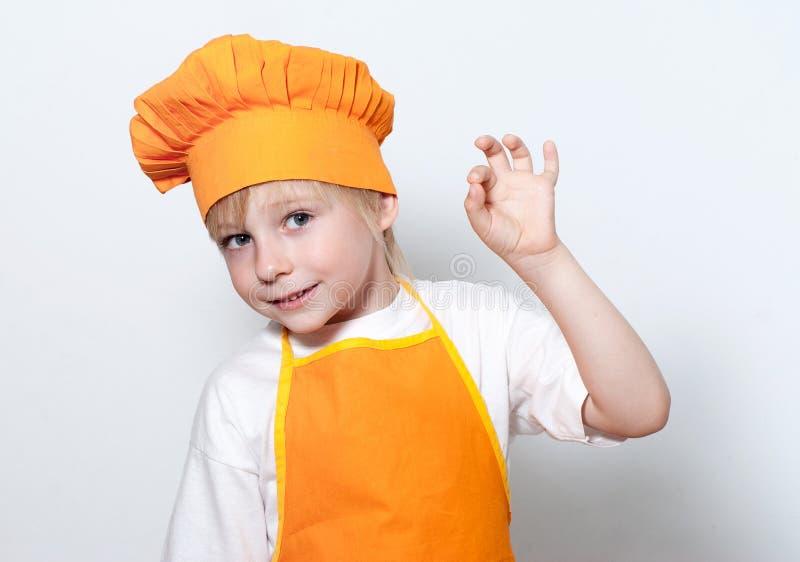 Criança como um cozinheiro do cozinheiro chefe foto de stock