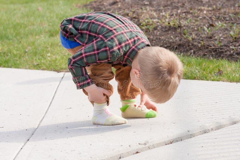 Criança confusa que olha suas duas peúgas diferentes imagem de stock