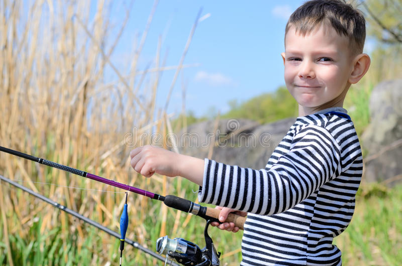 Criança considerável que guarda sua vara de pesca imagem de stock royalty free