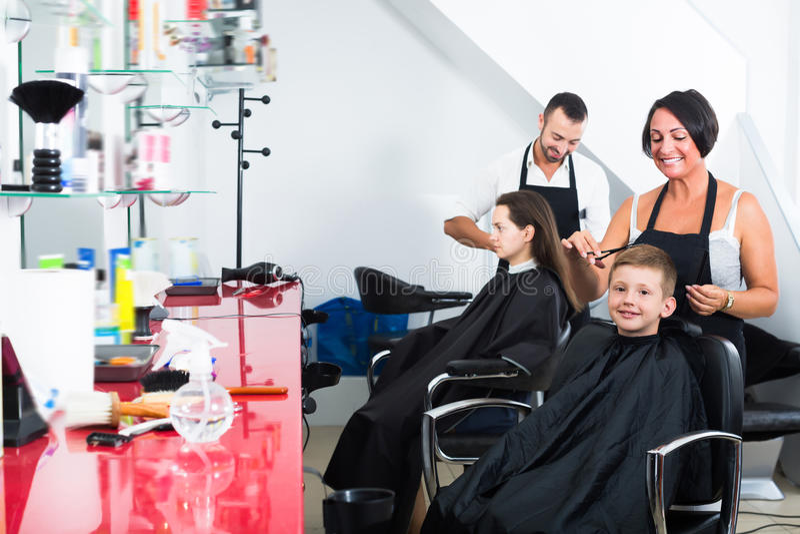 A criança contente que obtém o cabelo cortou pelo cabeleireiro da mulher fotografia de stock royalty free
