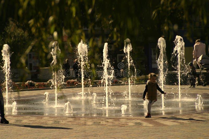 A criança corre longe do córrego da água na fonte imagem de stock
