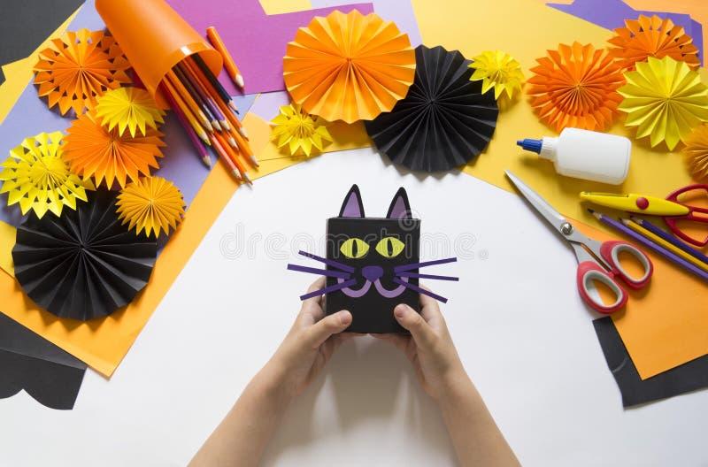 A criança cria uma caixa de presente de um gato preto Um partido para Dia das Bruxas imagens de stock royalty free