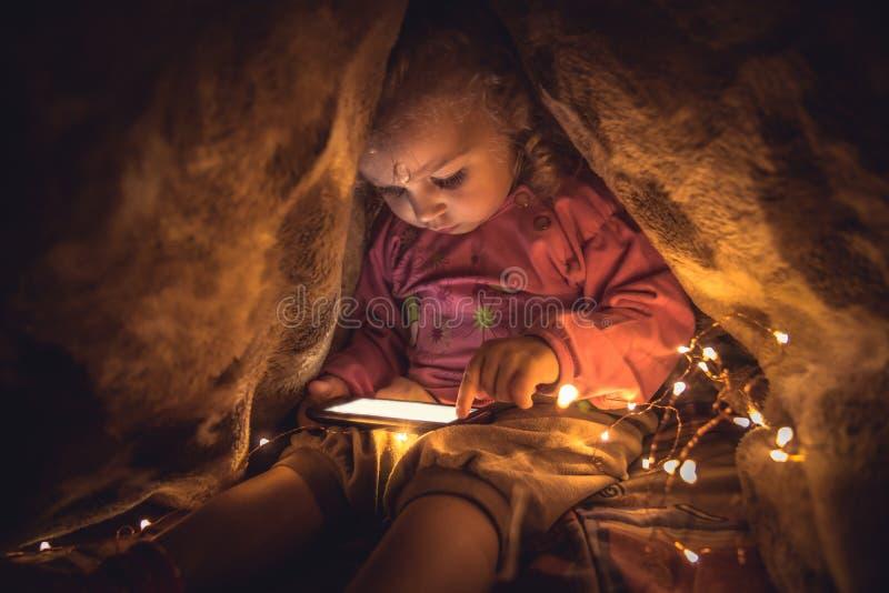Criança curiosa que joga com o telefone esperto que esconde no lugar secreto fotografia de stock