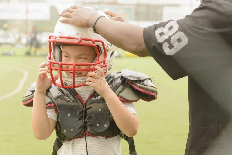 A criança da ajuda do treinador posta sobre o capacete prepara-se para jogar o futebol imagens de stock