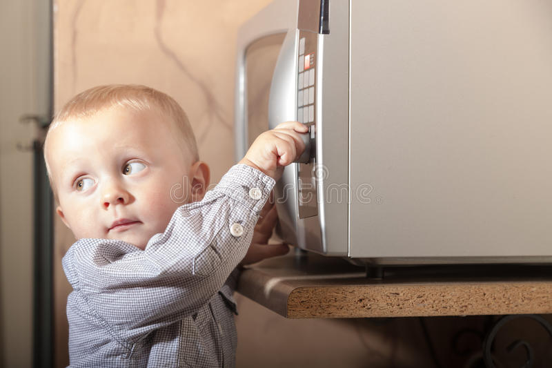 Criança da criança do menino que joga com o temporizador do forno micro-ondas fotos de stock