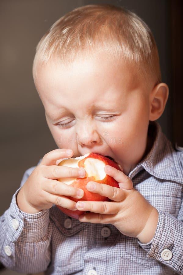 Criança da criança do rapaz pequeno que come o fruto da maçã em casa fotos de stock