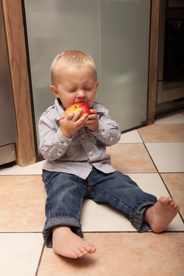 Criança da criança do rapaz pequeno que come o fruto da maçã em casa fotografia de stock royalty free