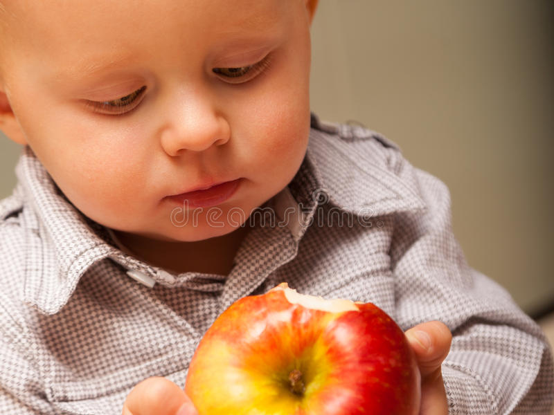 Criança da criança do rapaz pequeno que come o fruto da maçã em casa fotos de stock royalty free