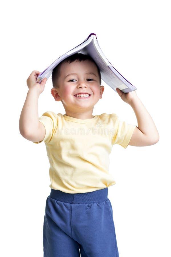 Criança da criança em idade pré-escolar com um livro sobre sua cabeça imagens de stock