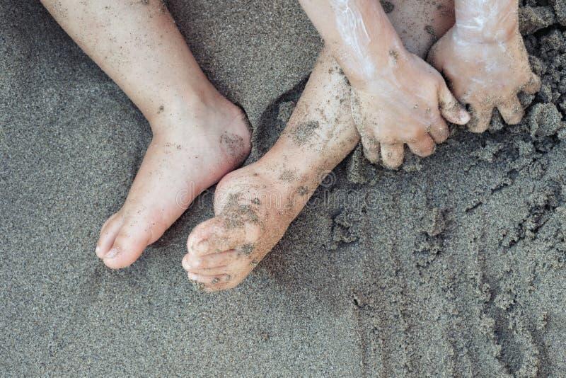 Criança da criança que joga na areia da praia com proteção solar no fim acima opinião superior dos fundos do feriado da praia fam foto de stock royalty free