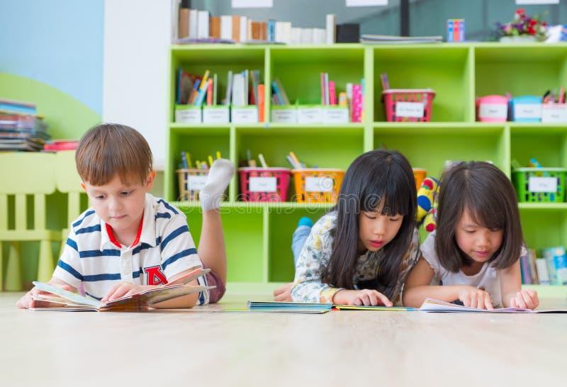 A criança da diversidade estabelece no livro do conto do assoalho e da leitura no prescho foto de stock royalty free