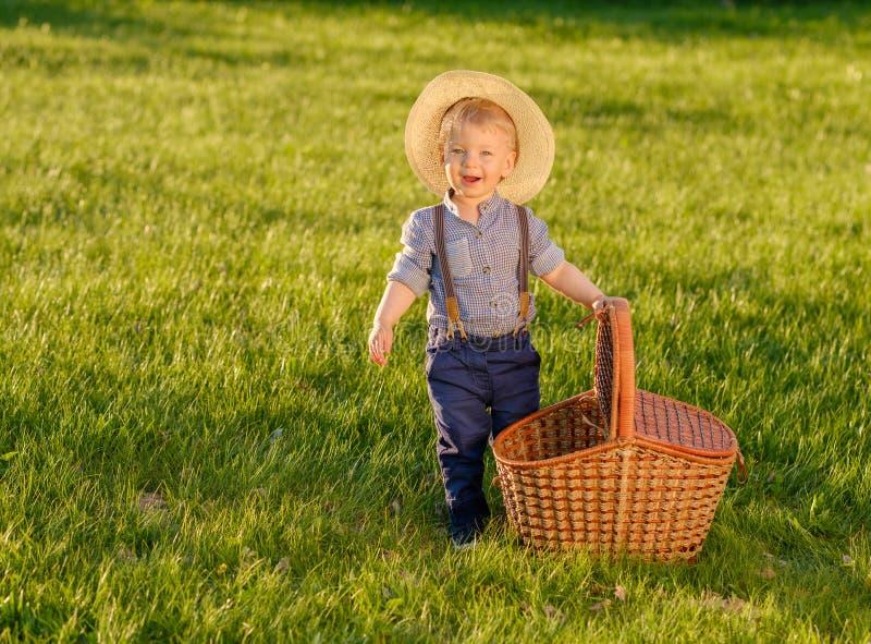 Criança da criança fora Chapéu de palha vestindo do bebê do bebê de um ano com cesta do piquenique imagens de stock