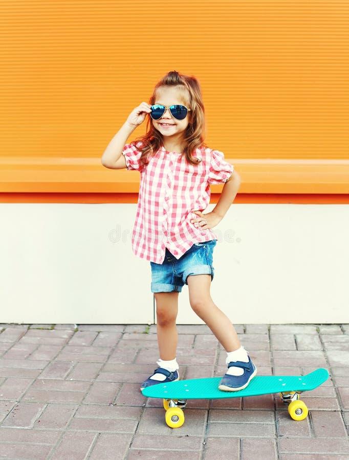 Criança da forma - criança à moda de sorriso da menina com os óculos de sol vestindo do skate na cidade fotografia de stock royalty free