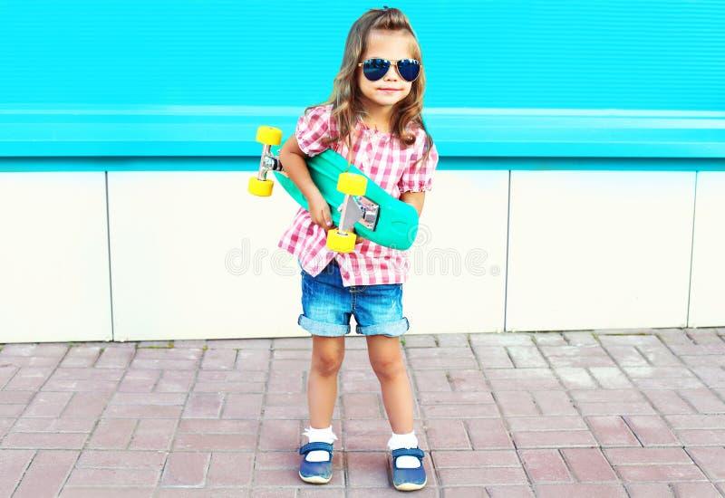 A criança da forma guarda o skate na cidade foto de stock