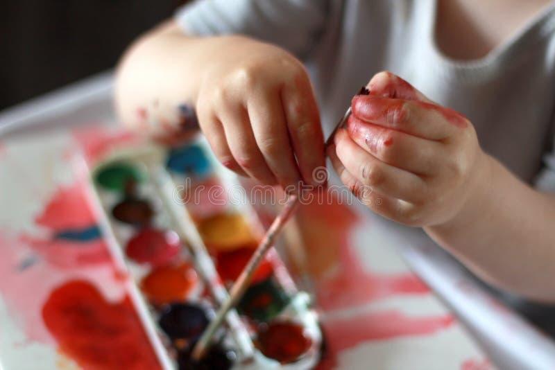 A criança da foto toca na escova com mãos sujas na pintura contra um fundo da pintura da aquarela fotografia de stock