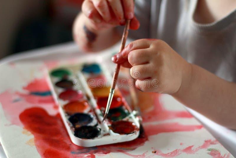A criança da foto toca na escova com mãos sujas na pintura contra um fundo da pintura da aquarela foto de stock royalty free