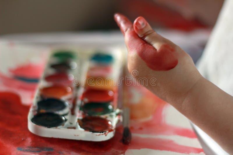A criança da foto toca na pintura em suas mãos M?os na pintura contra um fundo da pintura da aquarela imagens de stock