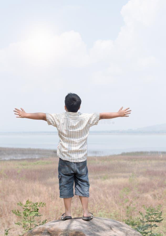 Criança da liberdade e da felicidade na represa Está apreciando a água sereno fotos de stock royalty free