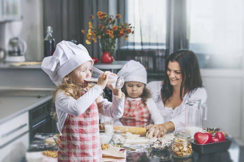 A criança da menina bebe o leite com suas mãe e irmã c feliz imagem de stock royalty free