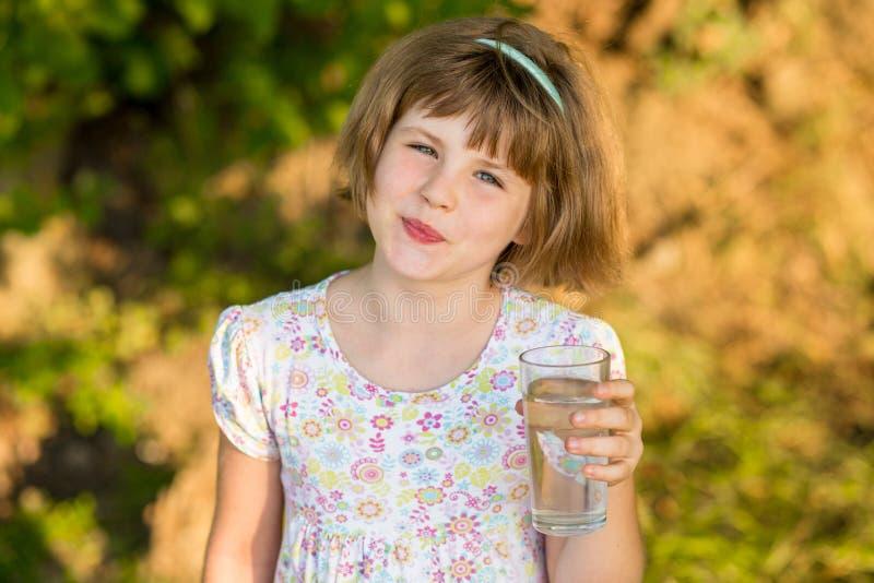 A criança da menina com vidro da água na manhã, bebe cada dia imagens de stock
