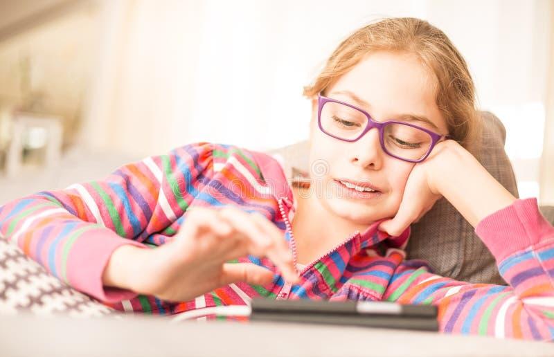 Criança da menina da criança que joga o jogo no telefone celular em casa imagem de stock royalty free
