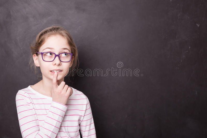 Criança da menina do aluno, aluno que pensa no quadro-negro foto de stock