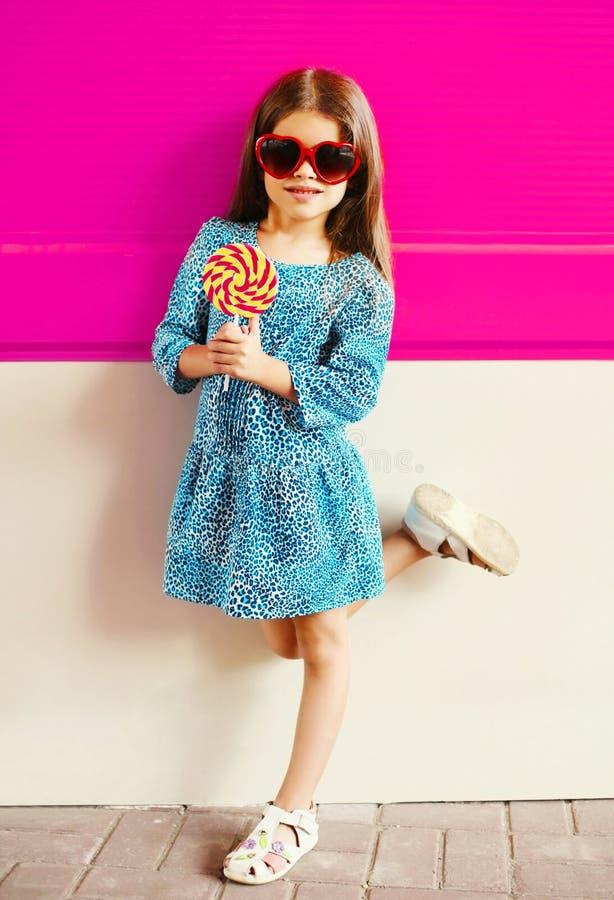 Criança da menina do retrato com a vara do pirulito no vestido azul do leopardo na parede cor-de-rosa colorida imagem de stock royalty free