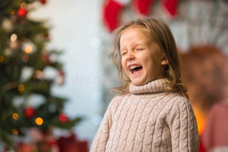 A criança da menina em casa na chaminé comemora o Feliz Natal w imagens de stock royalty free