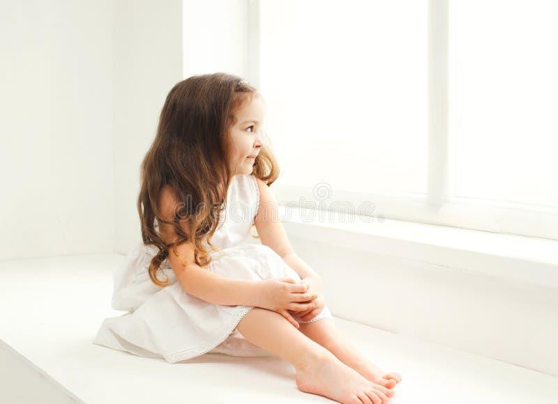 Criança da menina em casa no assento da sala branca fotografia de stock