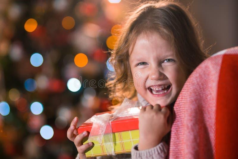 Criança da menina em casa pelos wi da chaminé e da árvore de Natal foto de stock royalty free