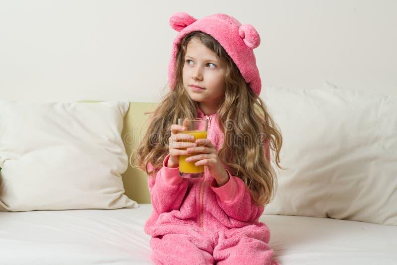 A criança da menina em um pijama encapuçado senta-se na cama em casa e bebe-se o suco de laranja imagem de stock royalty free