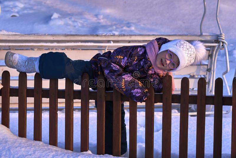 A criança da menina escala a cerca O tempo do divertimento é infância Noite ensolarada do inverno Por do sol fotografia de stock