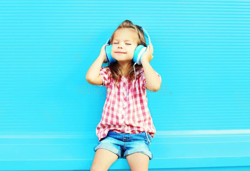 A criança da menina escuta a música nos fones de ouvido imagens de stock royalty free