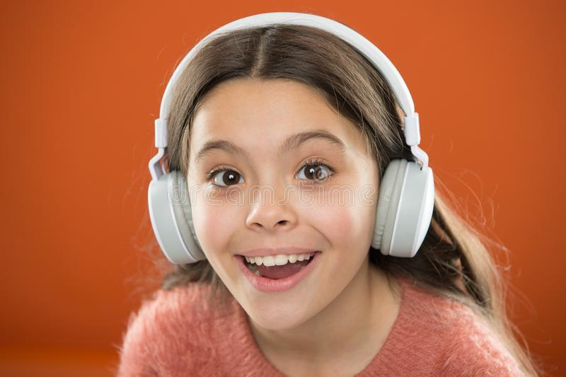 A criança da menina escuta música que os fones de ouvido modernos se fecham acima Obtenha a assinatura da música Acesso a milhões foto de stock royalty free