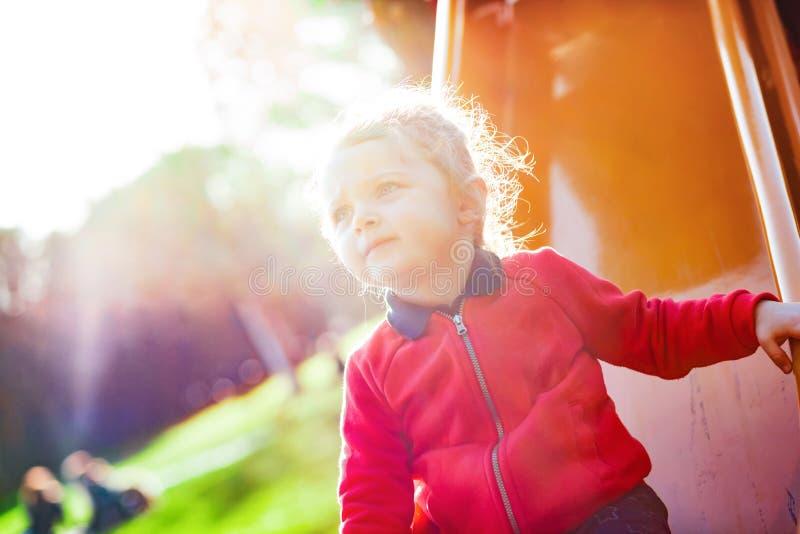 A criança da menina joga na corrediça no parque fotos de stock royalty free