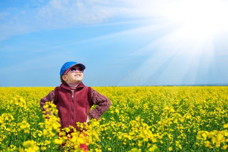 Criança da menina no campo com as flores amarelas brilhantes, paisagem da colza da mola fotografia de stock