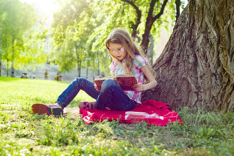 Criança da menina no livro de leitura dos vidros no parque, na grama perto da árvore fotos de stock
