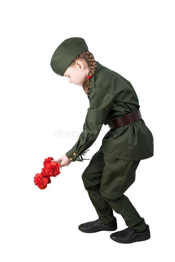 a criança da menina no uniforme militar coloca as flores vermelhas isoladas no branco imagens de stock royalty free