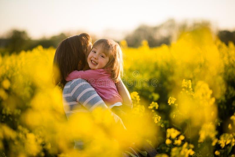 Criança da menina que abraça sua mãe loving no campo da colza imagem de stock