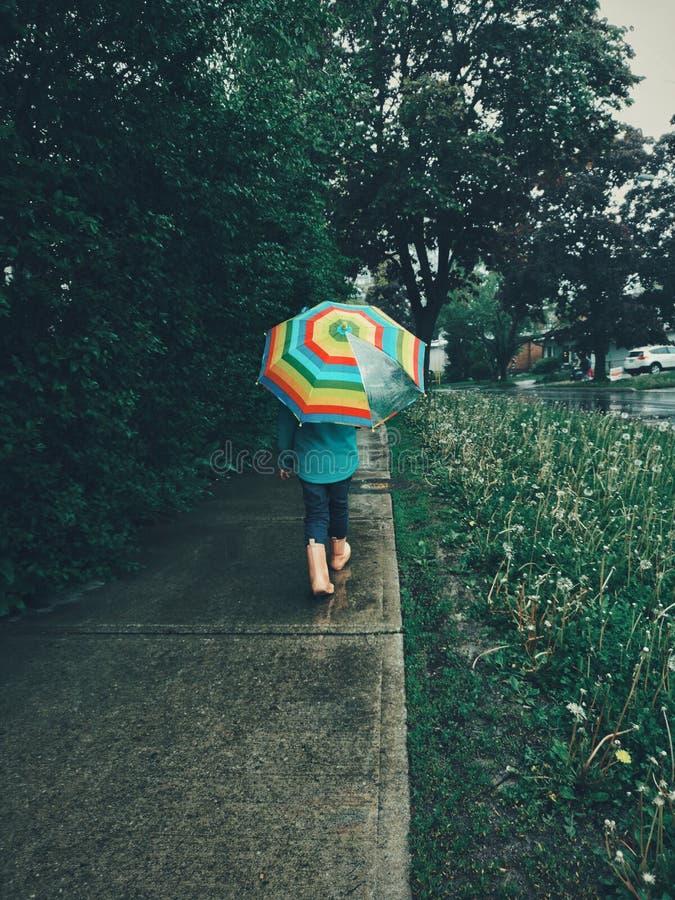 Criança da menina que anda na estrada da rua sob a chuva com guarda-chuva do arco-íris fotos de stock
