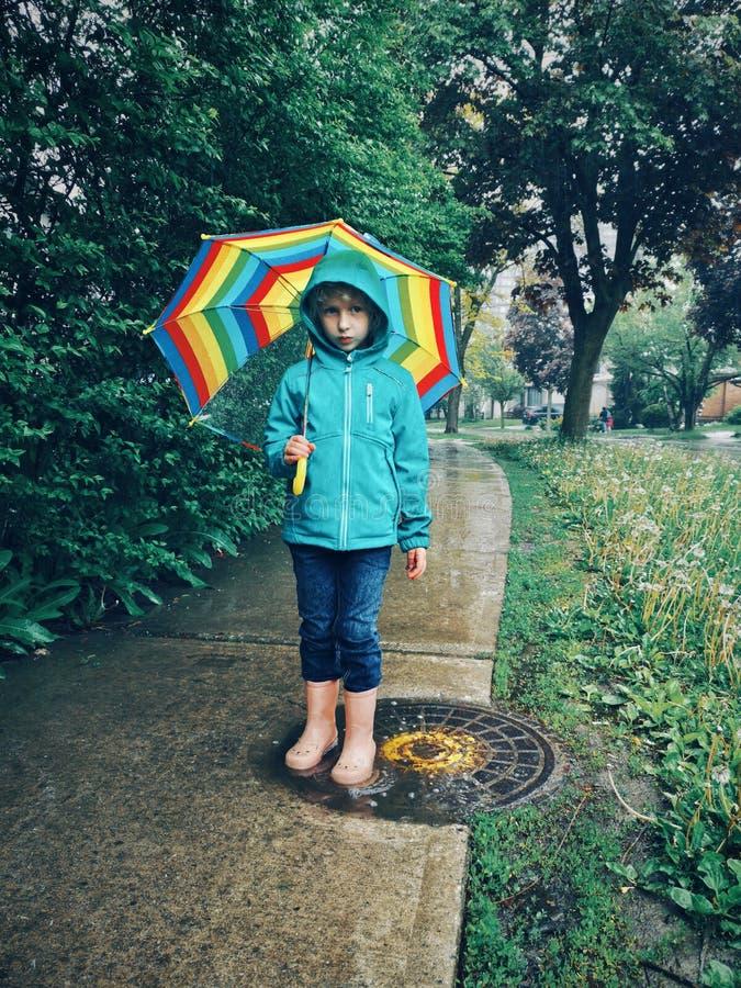 Criança da menina que anda na estrada da rua sob a chuva com guarda-chuva do arco-íris imagens de stock royalty free