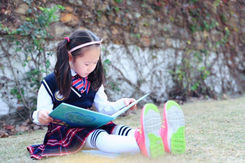 Criança da menina que lê um livro na grama imagem de stock royalty free