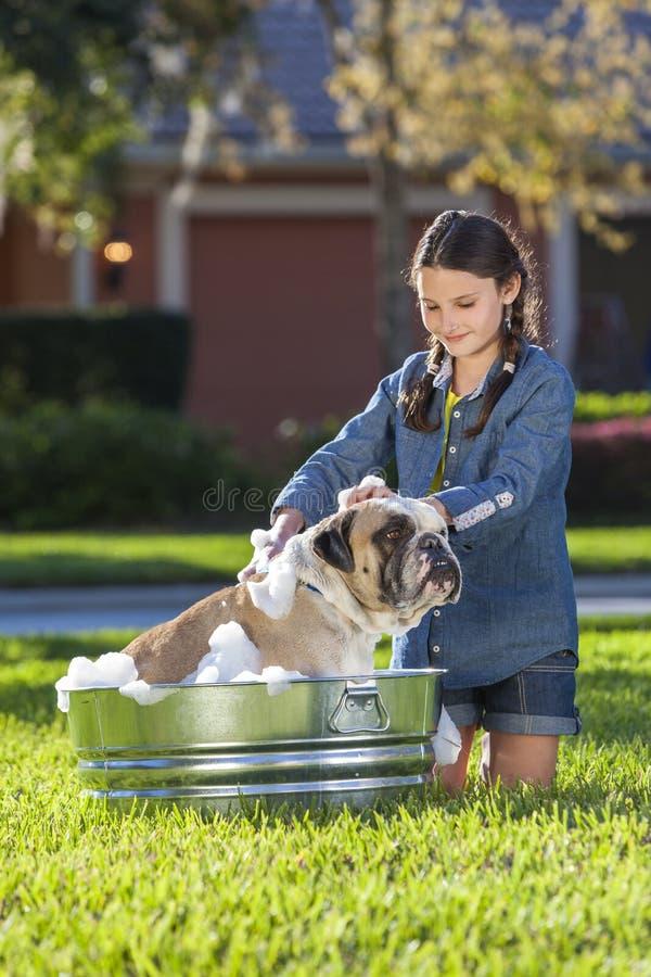 Criança da menina que lava seu cão de estimação em uma cuba fotografia de stock royalty free