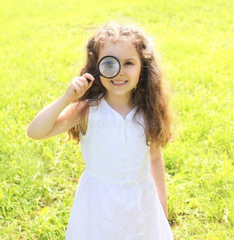 Criança da menina que olha através de uma lupa na natureza imagem de stock royalty free