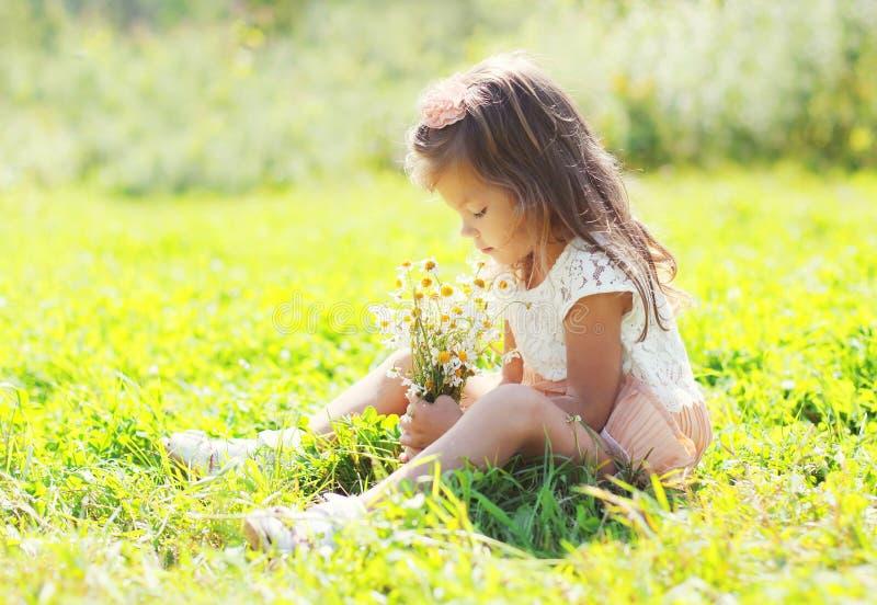 A criança da menina que senta-se com o ramalhete das camomilas floresce imagem de stock royalty free