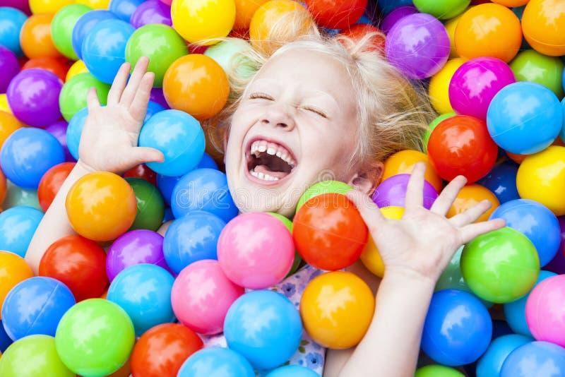 Criança da menina que tem o divertimento jogar em esferas coloridas fotografia de stock royalty free